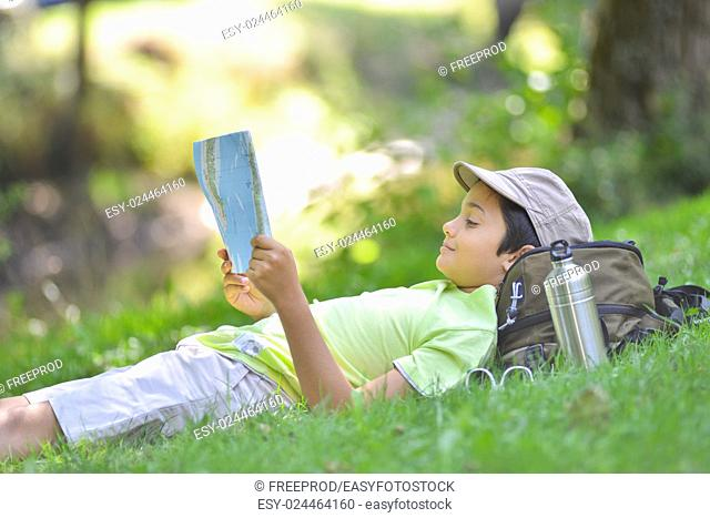 Young boy lying in the grass looking at a map