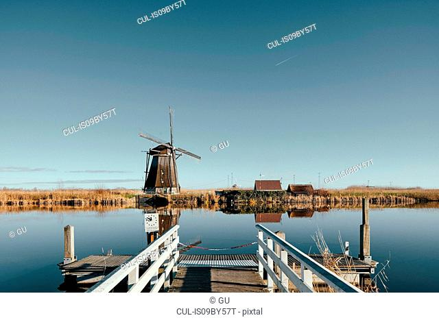 View of windmill along canal from pier, Kinderdijk, Zuid-Holland, Netherlands