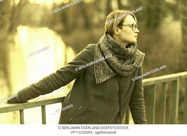 woman outdoors at bridge over river, at public park Englischer Garten in Munich, Germany