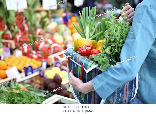 A woman at a market with a full shopping bag