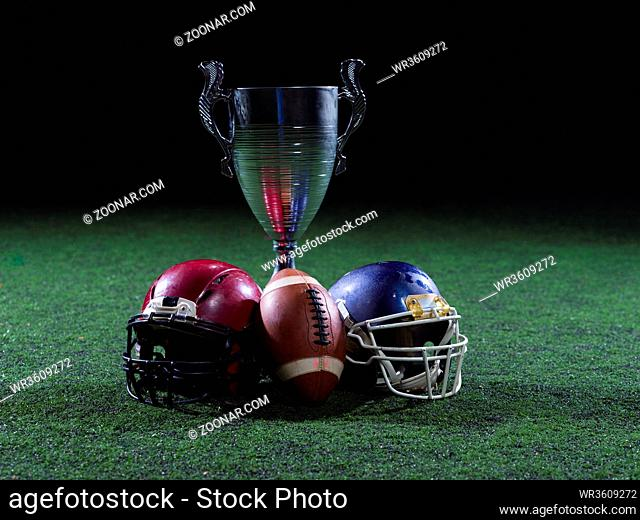 closeup shot of american football, helmets and trophy on grass field at night