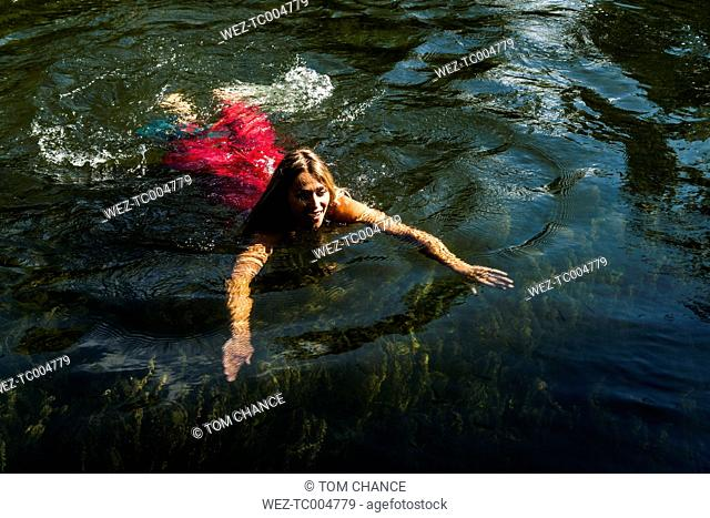 Woman in summer dress swimming in lake