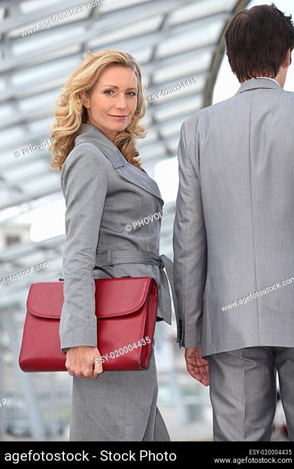 Woman carrying briefcase with colleague