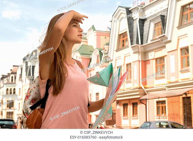 Waist-up portrait of pretty female traveler on the street holdin