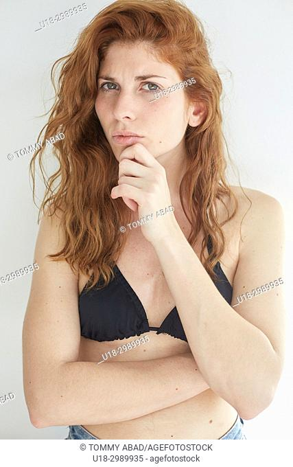 Half length portrait of young redhead woman wearing a black bikini, looking at camera with thoughtful expression