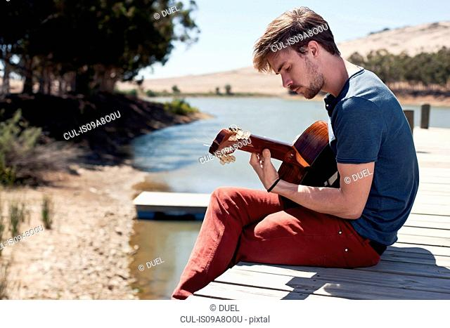 Young man sitting on pier playing guitar