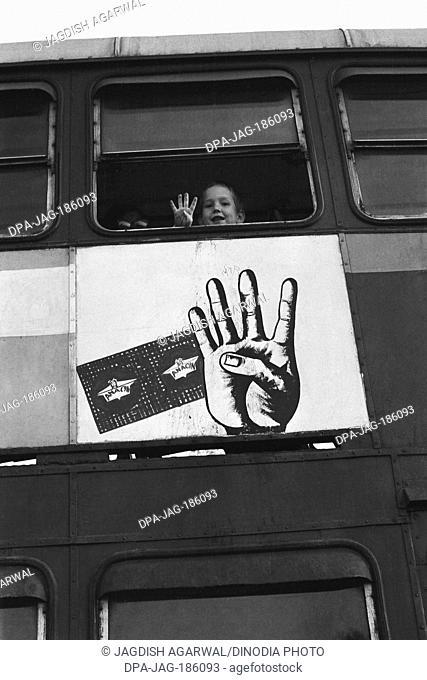 Child in bus showing four fingers imitating poster Mumbai Maharashtra India Asia 1974
