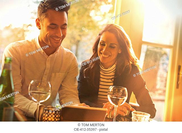 Young couple drinking wine and using digital tablet at sunny restaurant