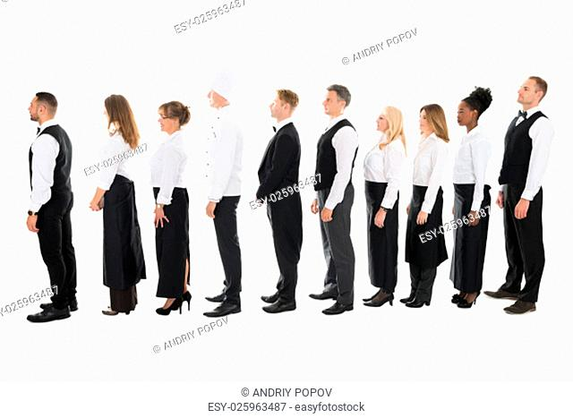 Full length side view of restaurant staff standing in line against white background