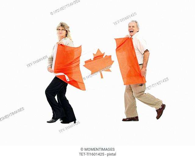 Two people carrying the Canadian flag