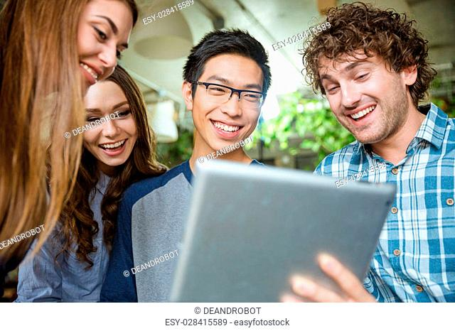 Amusing cheerful candid young people using tablet