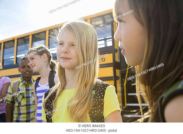Cute girl standing with friends by bus on field trip