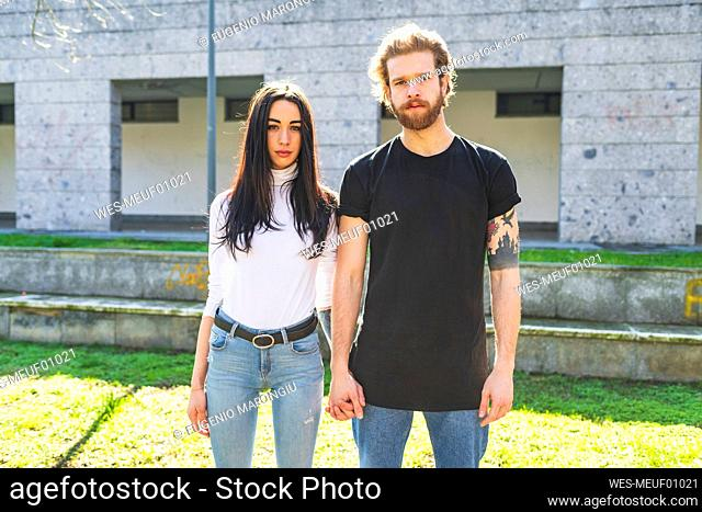 Young couple holding hands while standing against building
