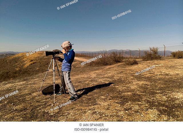 Boy looking through telescope on tripod