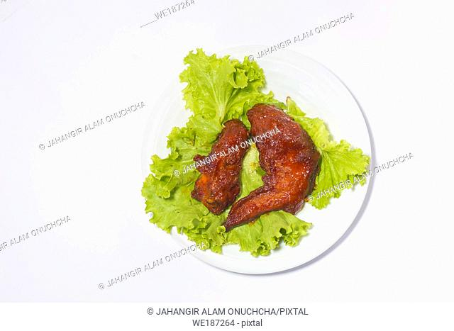 Baked chicken wings with sesame and lettuce with a plate. Top view