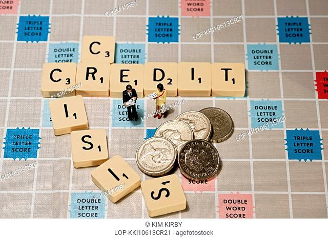 England, North Yorkshire, York. Tiles on a Scrabble board with a toy man and woman and English pound coins
