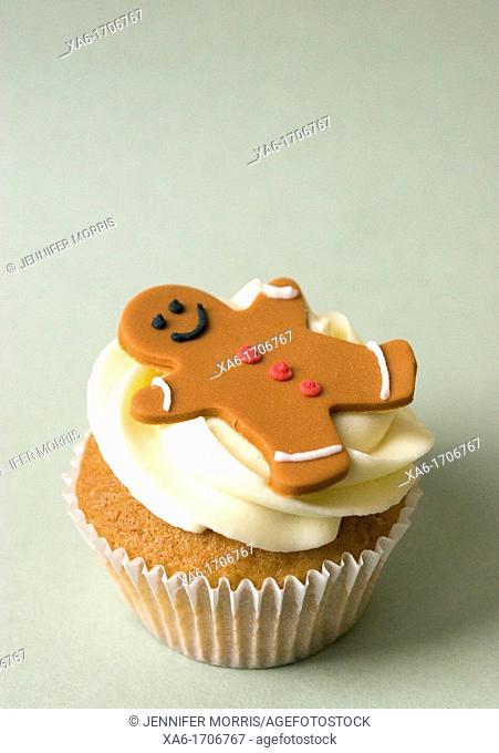 Three cupcakes with vanilla frosting swirls and gingerbread man decorations on