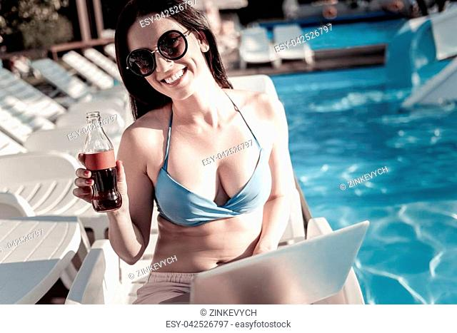 Waiting for you to join me. Cheerful young woman looking into the camera with a broad smile on her face while working on a laptop and holding a glass bottle of...
