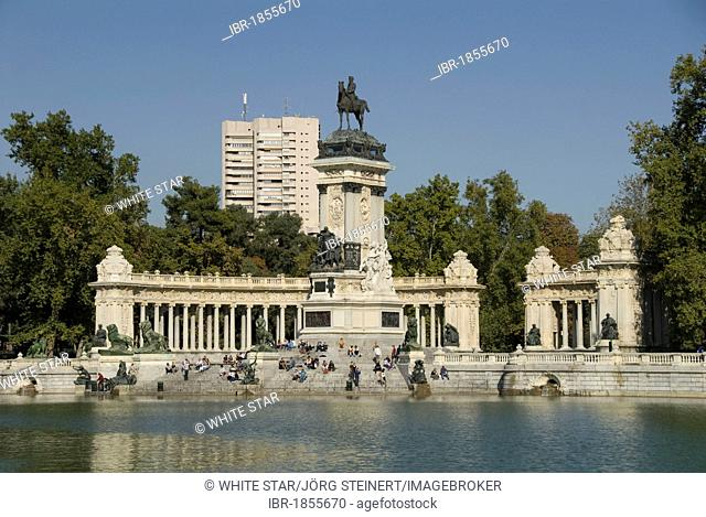 View over an artificial lake towards people in front of a monument with an equestrian statue of King Alfosno XII, Parque del Buen Retiro