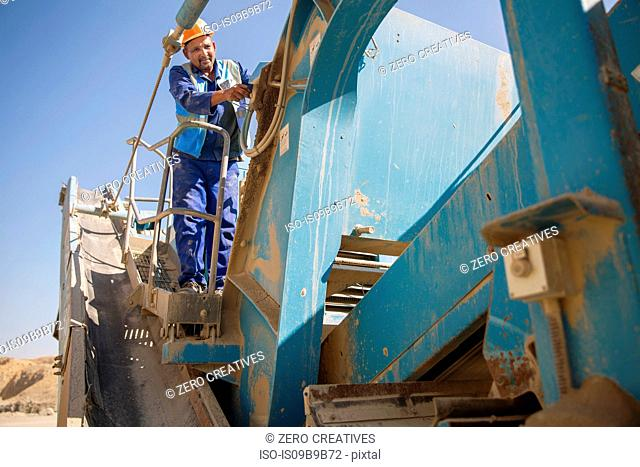 Quarry worker working on heavy machinery