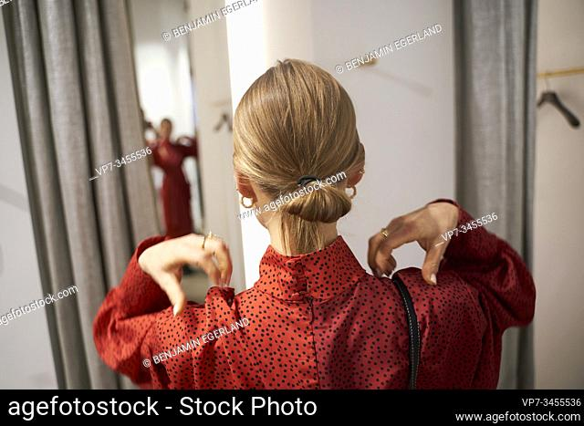 Woman trying on a red dress in front of a mirror in a clothing store