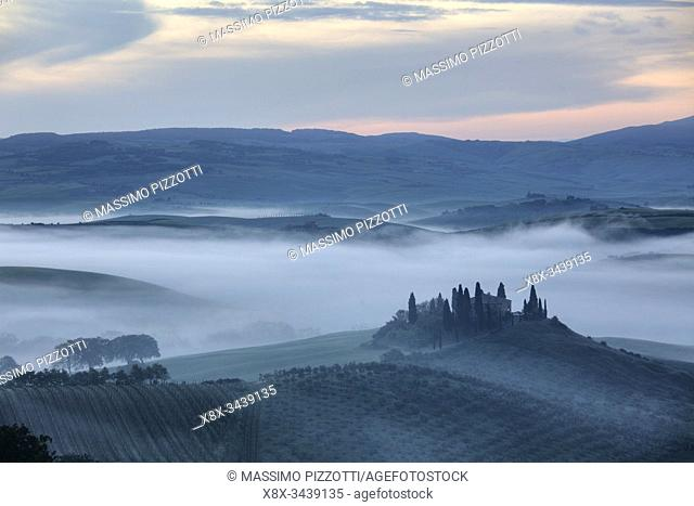 The Belvedere farmhouse in Val dâ. . Orcia with early morning fog, San Quirico d'Orcia, Tuscany, Italy