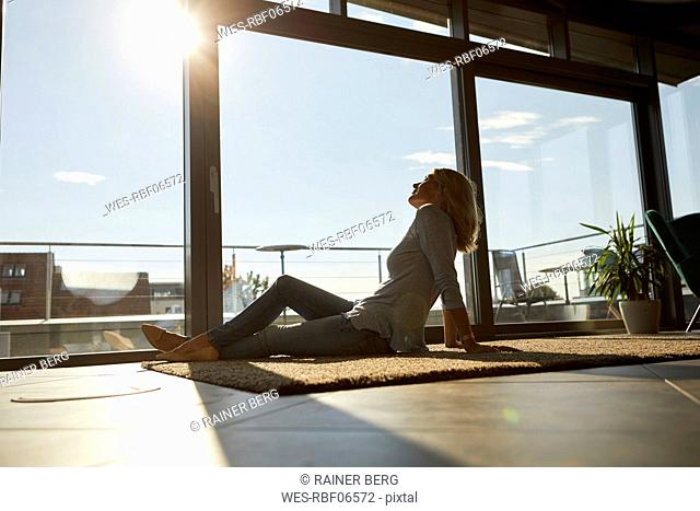 Relaxed mature woman sitting on carpet in sunlight at home