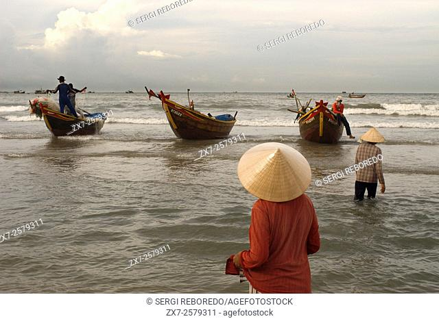 Lady awaiting the landing of the catch, Mui Ne fishing village, Bình Thuận Province, Vietnam
