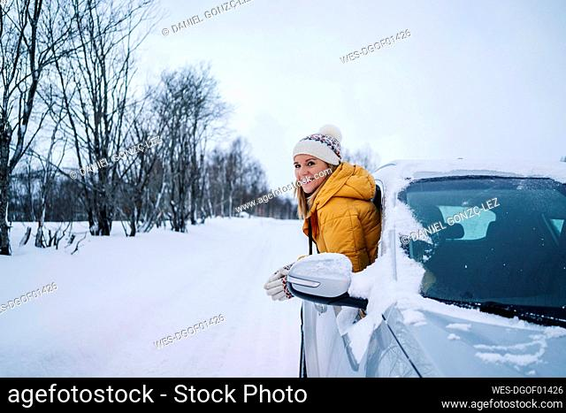 Smiling woman peeking through car window against sky during winter