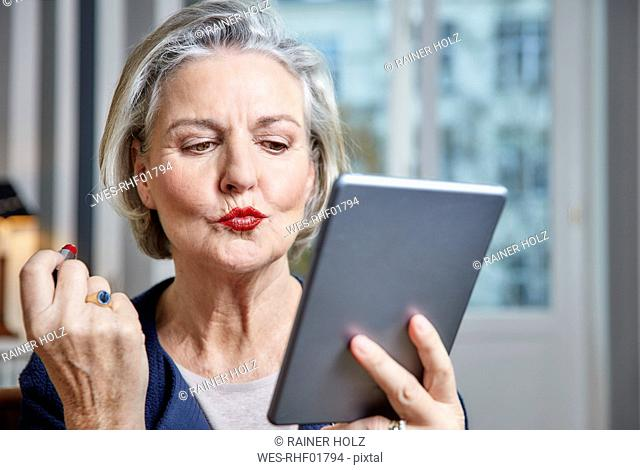 Senior woman applying lipstick holding tablet