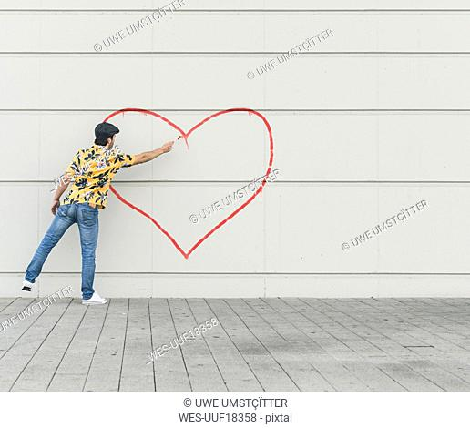 Digital composite of young man drawing aheart at a wall