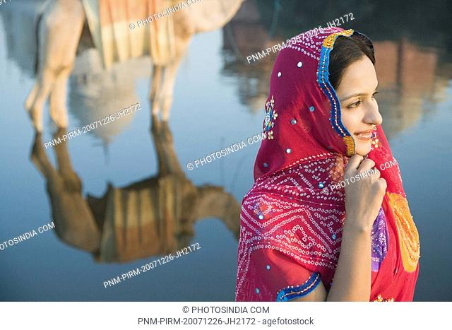 Woman with reflection of a camel and a mausoleum in the river, Taj Mahal, Yamuna River, Agra, Uttar Pradesh, India