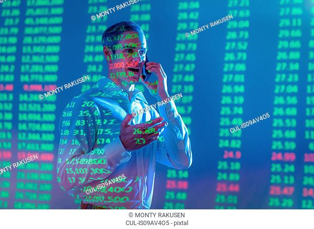 Businessman using mobile phone with projected financial data