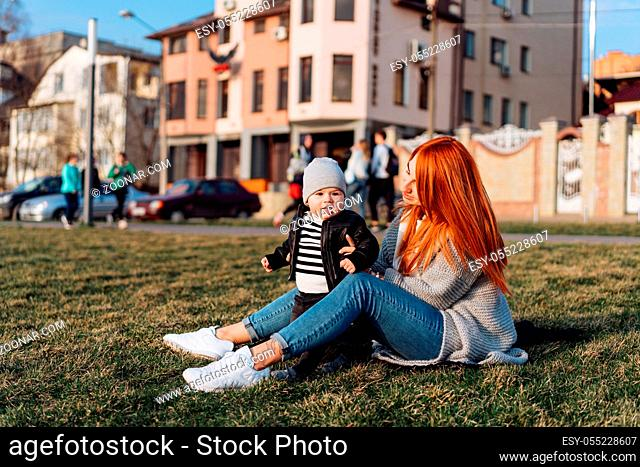 Mother and son on vacation on green grass sunny summer day. Family spending time together