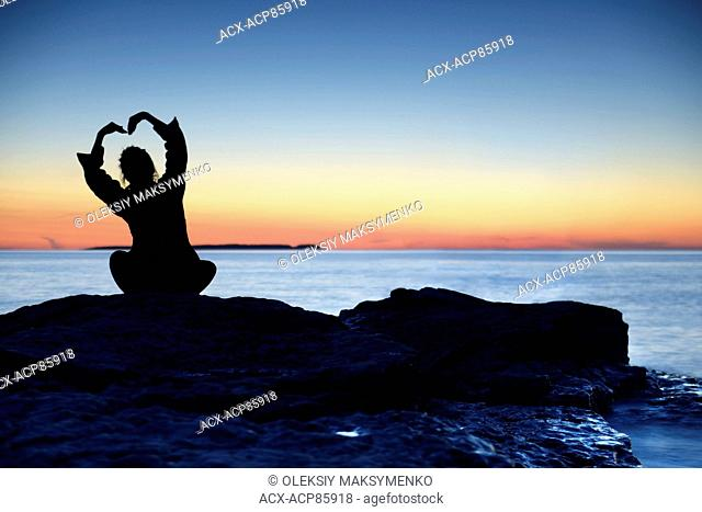 Silhouette of a woman sitting alone an a shore at sunset with her hands raise in a shape of a flower above her head, conceptual photo