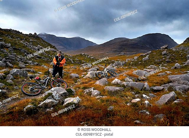 Male mountain biker taking a break in mountain valley landscape, Achnasheen, Scottish Highlands, Scotland