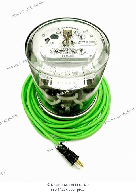 Electrical supply meter with a green electrical power cord and a black plug