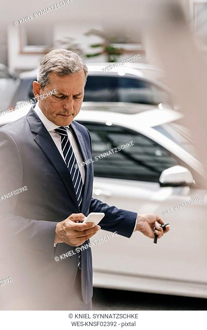 Businessman checking message while using remote control key of car