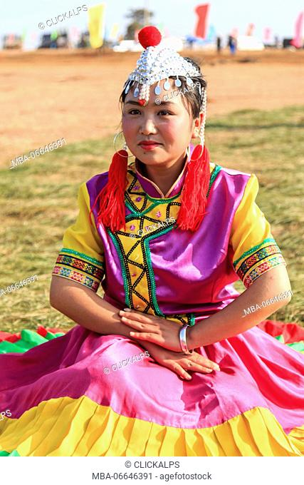 Chinese girl in traditional Chinese clothing during the Heqing Qifeng Pear Flower festival, China