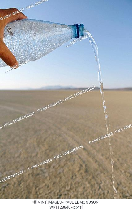 The landscape of the Black Rock Desert in Nevada. An essential element for survival. A bottle of water being poured out. Filtered mineral water