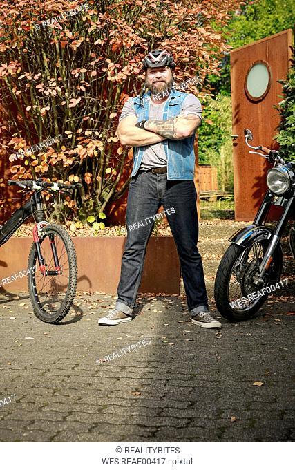 Portrait of man standing between motorbike and bicycle
