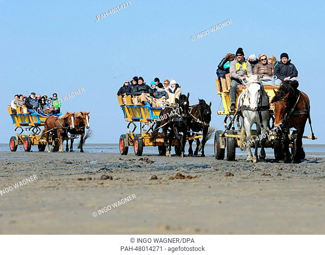 Easter holiday vacationers return from the North Sea Island Neuwerk to the Beach of Duhnen in carriages during ebb tide and mild spring weather in Cuxhaven