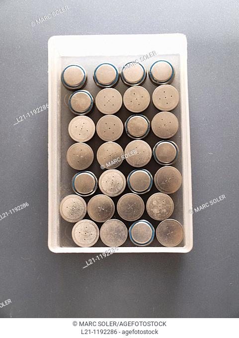 Button batteries in a white box for recycling