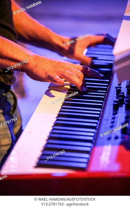 hand playing on a keyboard in concert