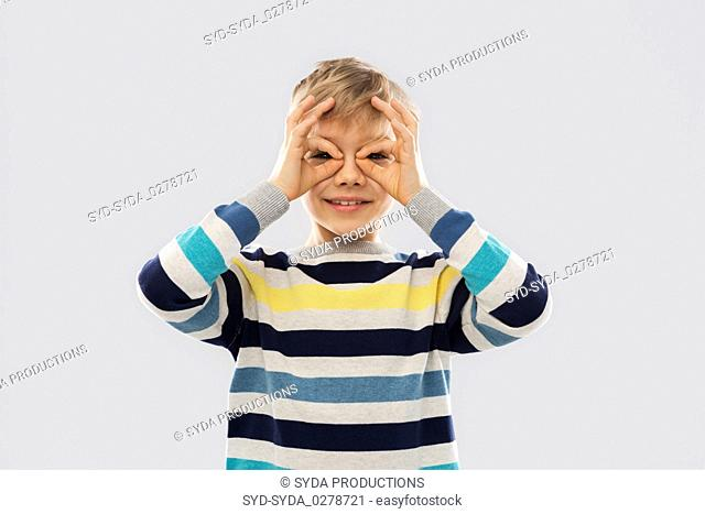 boy in pullover looking through finger glasses
