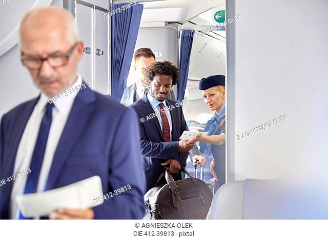 Flight attendant helping businessman with boarding pass on airplane