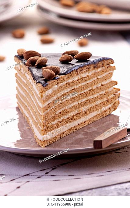 A slice of layered chocolate, toffee and almond cream cake decorated with almonds