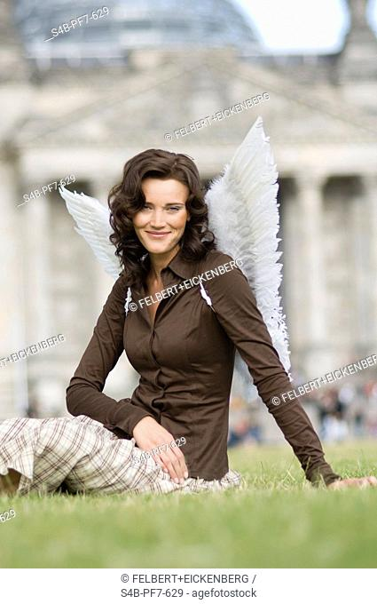 Woman with angel wings sitting in meadow at the Reichstag, Berlin, Germany