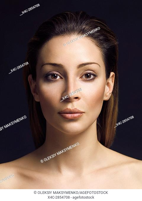 Beauty portrait of a young exotic woman with brown hair and clean natural makeup, closeup of face isolated on black background