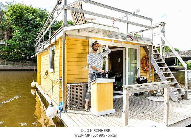 Man wearing captain's hat having a trip on a house boat